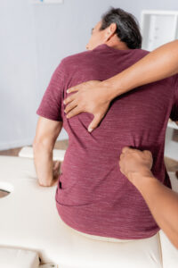 A chiropractor massaging the back of a man who sits on a white massage table.